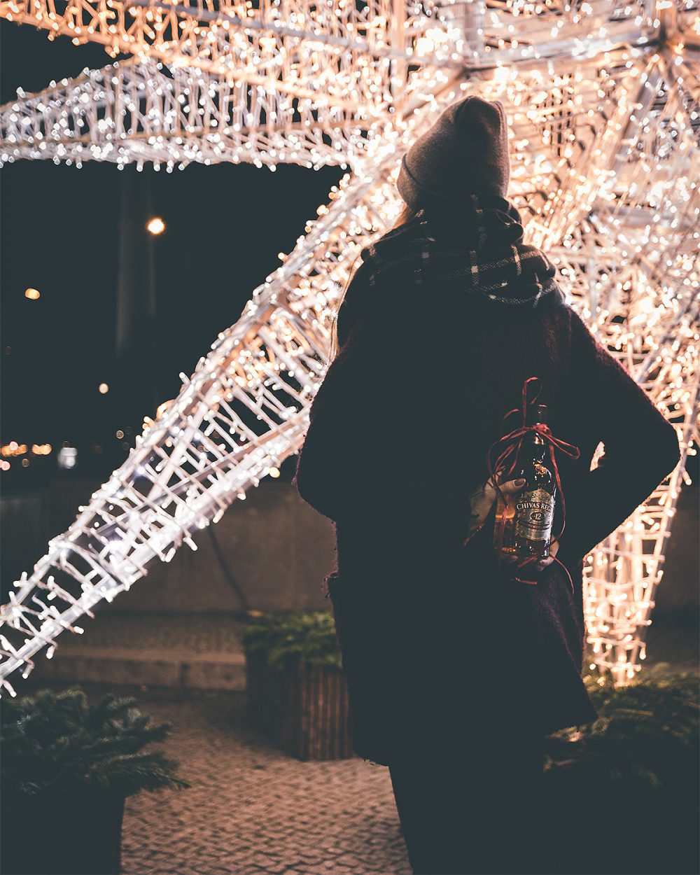 Woman holding bottle of Chivas behind her back and stnading infornt of a huge Christmas star light, shot by influencer Zerletti