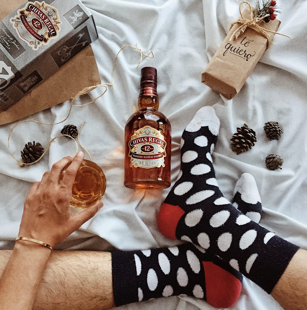 Winter gifter sat with his Chivas whiskey in Christmas socks