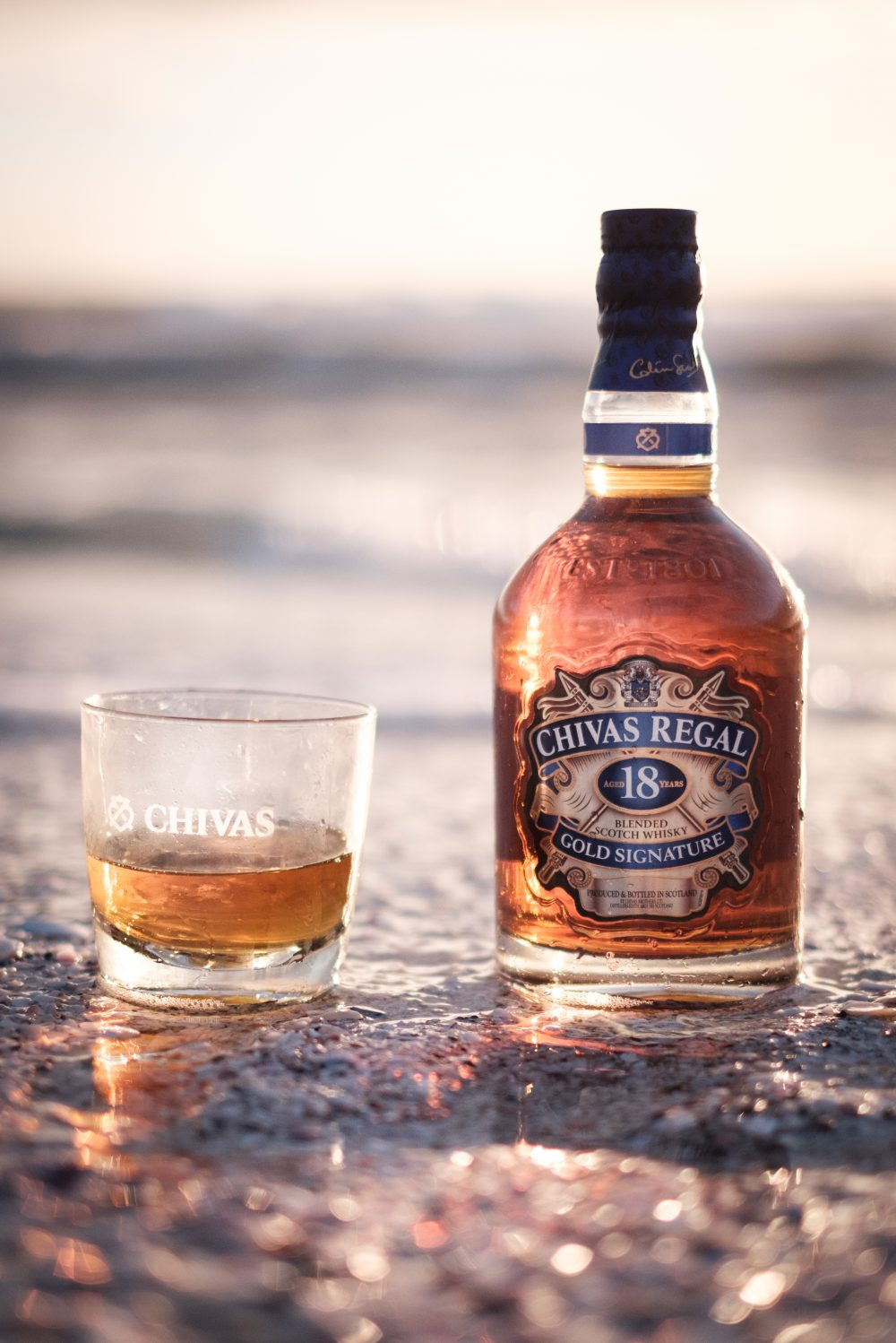 Bottle of Chivas and whiskey glass on the beach, shot by influencer Zerletti